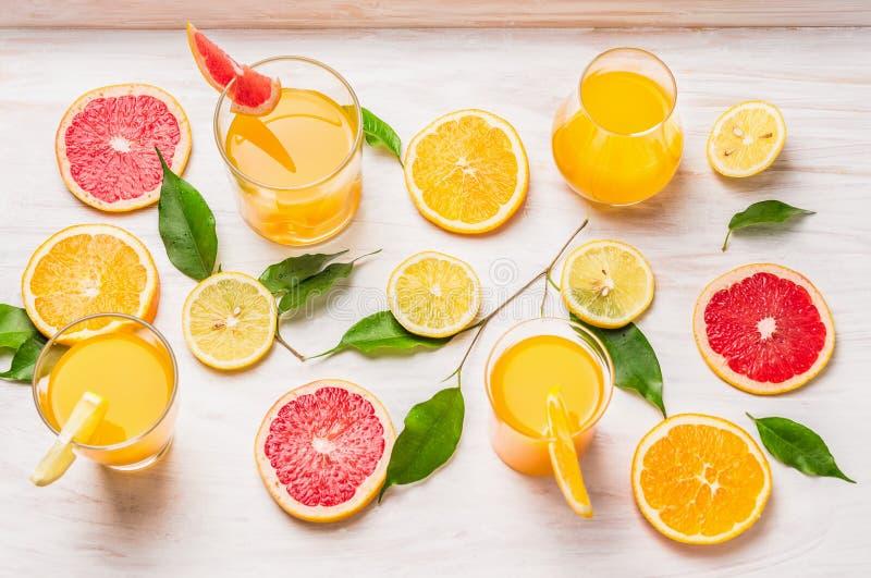 Jugos de la fruta cítrica en vidrio y una rebanada de naranja, de pomelo y de limón foto de archivo libre de regalías