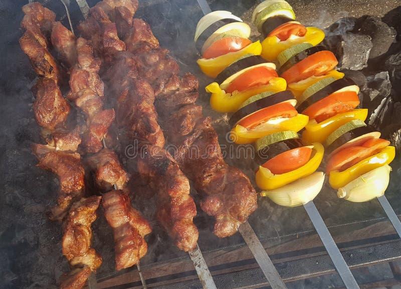 Jugoso adobado en kebab de la carne de las especias en los pinchos, cocinado y frito en una parrilla de la barbacoa del fuego y d fotografía de archivo