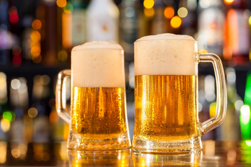 Jugs of beer served on bar counter royalty free stock photo