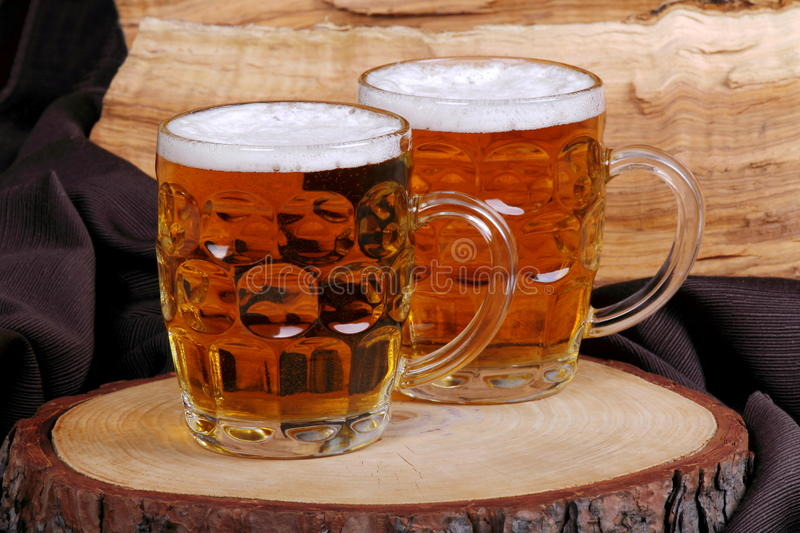 Jugs of blonde beer. On trunk of pine with background servant with wood of ulivo and brown cloth stock photography