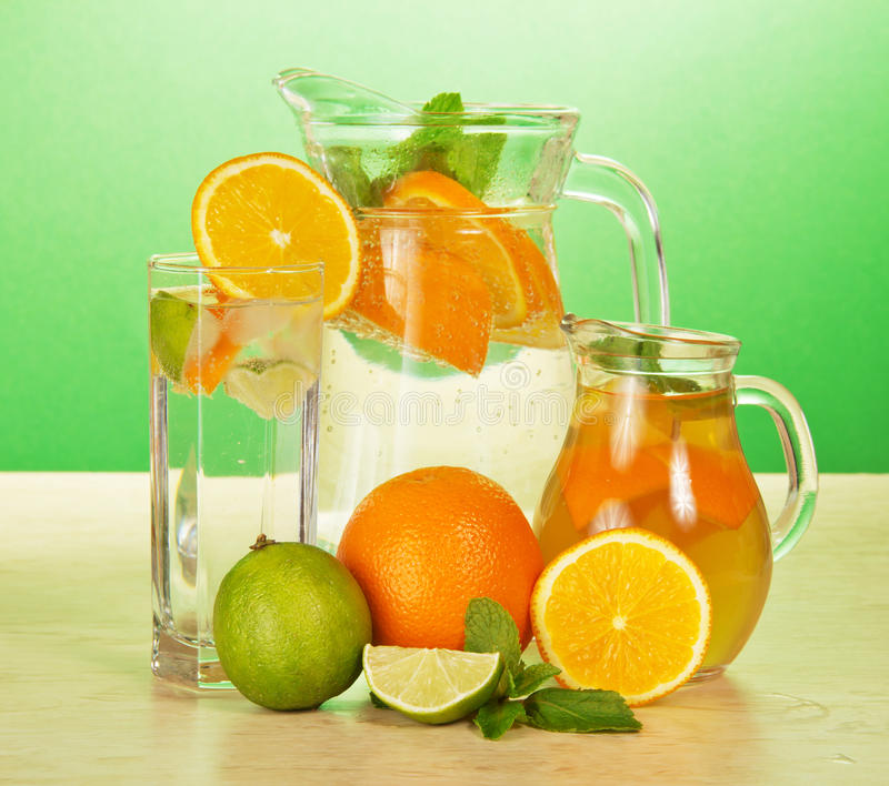 Jugs and glass with oranges juicy. Jugs with drinks, a glass, a juicy lime and oranges on a table stock photos