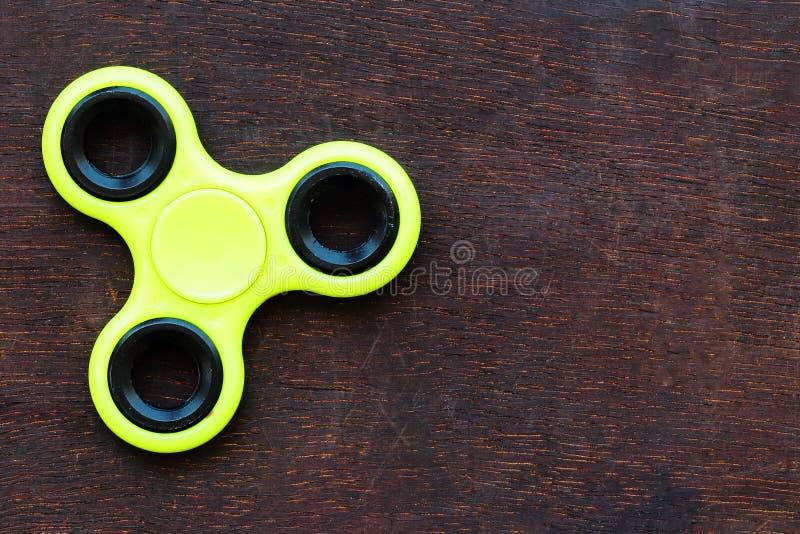 Juguete amarillo del alivio de tensión del HILANDERO de la persona agitada en fondo de madera imágenes de archivo libres de regalías