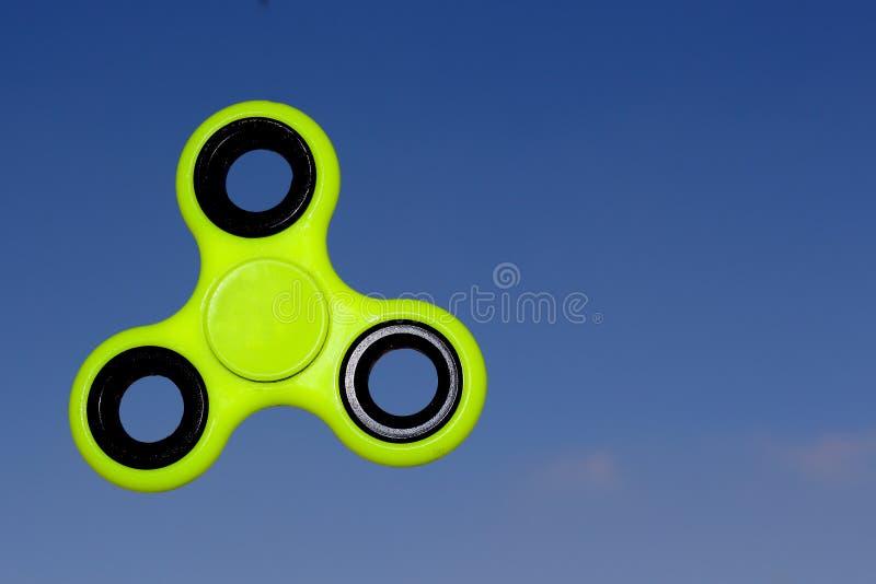 Juguete amarillo del alivio de tensión del HILANDERO de la persona agitada en fondo del cielo foto de archivo