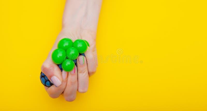 Juguete antiesfuerzo en mano femenina en fondo amarillo fotografía de archivo libre de regalías