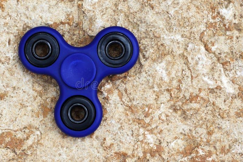 Juguete azul del alivio de tensión del HILANDERO de la persona agitada en el fondo de piedra Es fotos de archivo