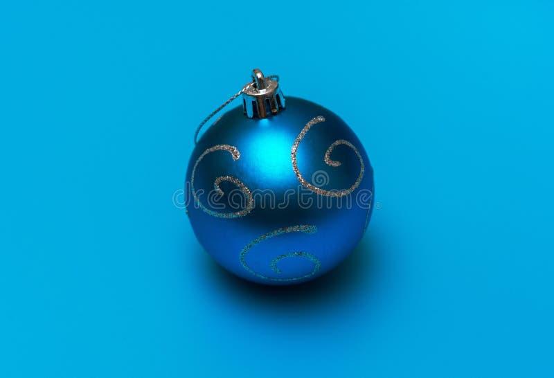 juguete azul navideño con espirales plateadas para la decoración en un fondo turquesa imagenes de archivo