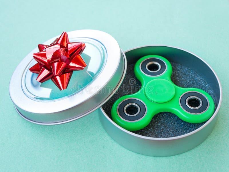 Juguete colorido popular del hilandero de la persona agitada en una caja de regalo en un fondo coloreado fotografía de archivo