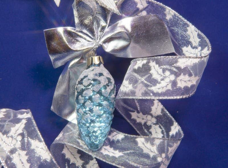 Juguete de cristal hermoso de un cono, malla brillante blanca en un fondo azul - composición del ` s del Año Nuevo, una tarjeta d foto de archivo libre de regalías