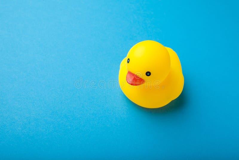 Juguete de goma amarillo del pato en fondo azul fotos de archivo