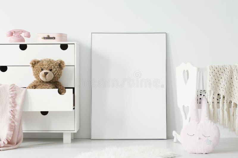 Juguete de la felpa en gabinete al lado del cartel con la maqueta y cuna en vagos imagen de archivo libre de regalías