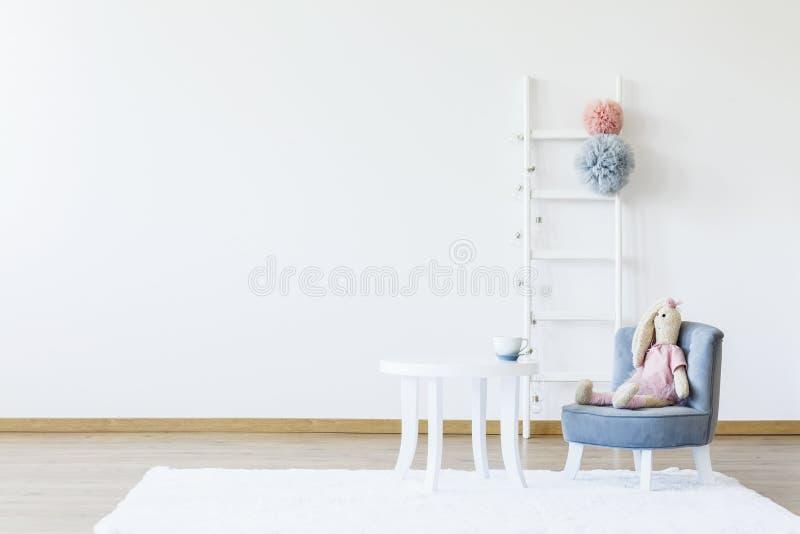 Juguete de la felpa en silla gris en la tabla blanca en el sitio mínimo i del ` s del niño imagenes de archivo