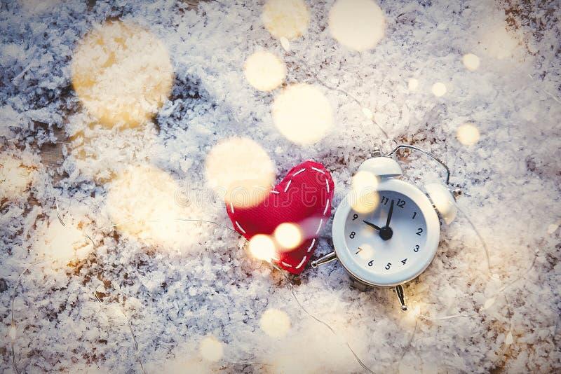 Juguete de la forma del corazón y luces de hadas con el despertador en backgr de la nieve foto de archivo