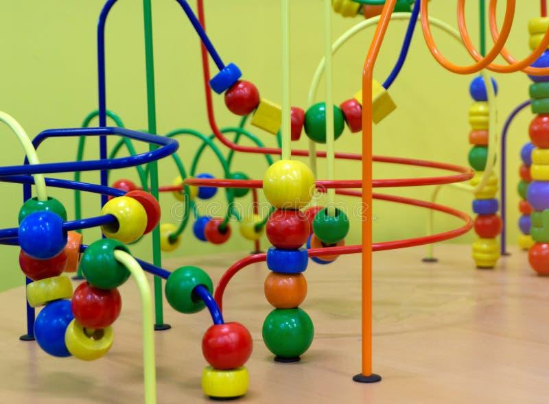 Juguete de madera educativo de la lógica con las trayectorias en bebé del niño en sitio del cuarto de niños foto de archivo
