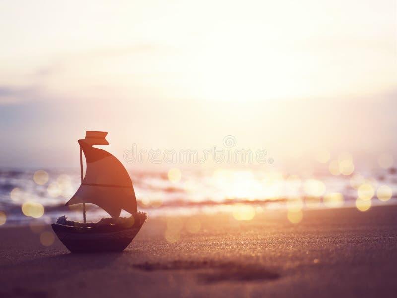 Juguete del bote pequeño de la silueta en la arena en la playa de la puesta del sol fotos de archivo libres de regalías