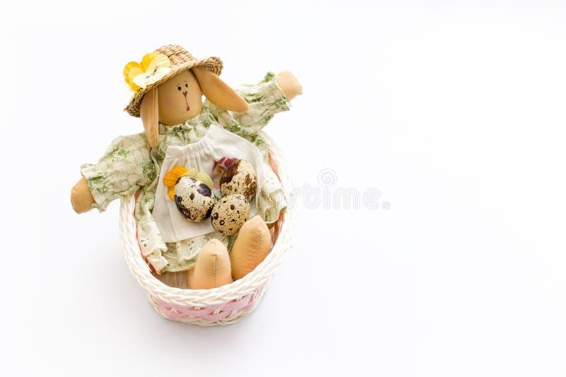Juguete del conejito de pascua en una cesta rosada con los huevos de codornices en el fondo blanco imagenes de archivo