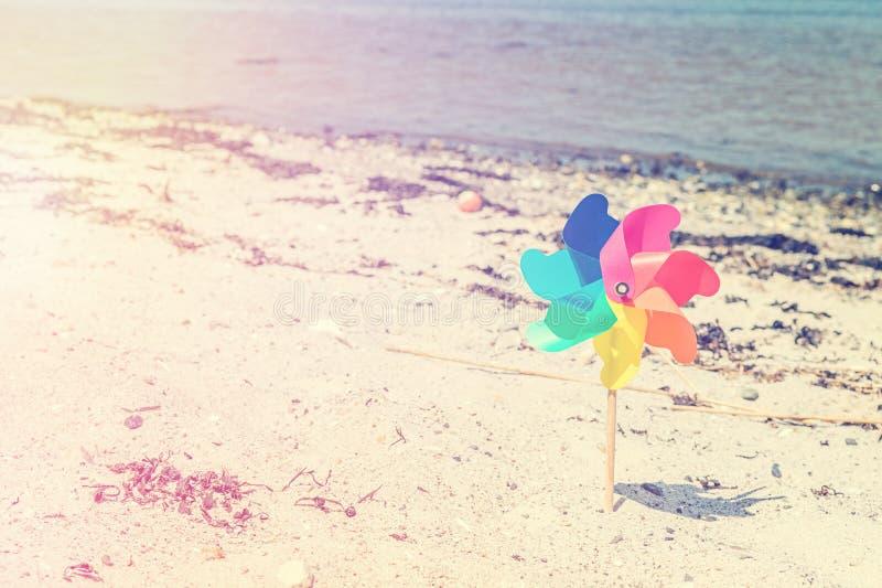 Juguete del molino de viento en una playa foto de archivo