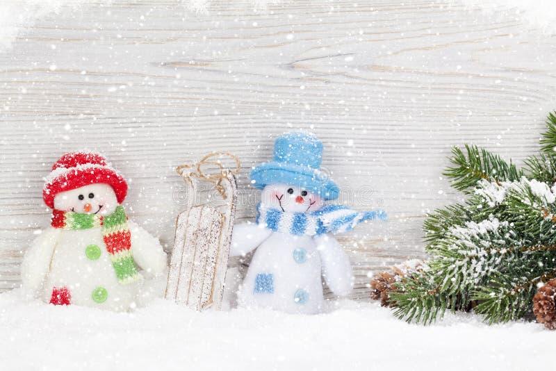 Juguete del muñeco de nieve de la Navidad, decoración y rama de árbol de abeto imagenes de archivo