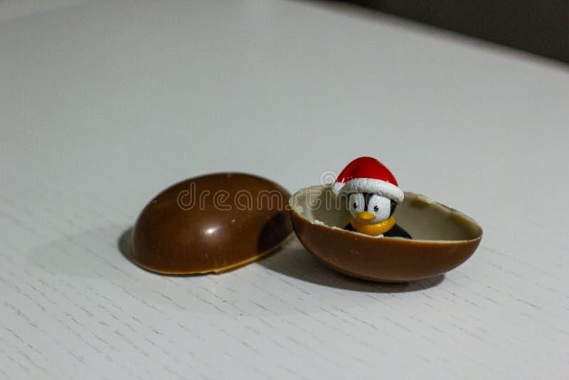 Juguete del pingüino en el huevo de chocolate Niñez en mi corazón kinder sorpresa fotografía de archivo