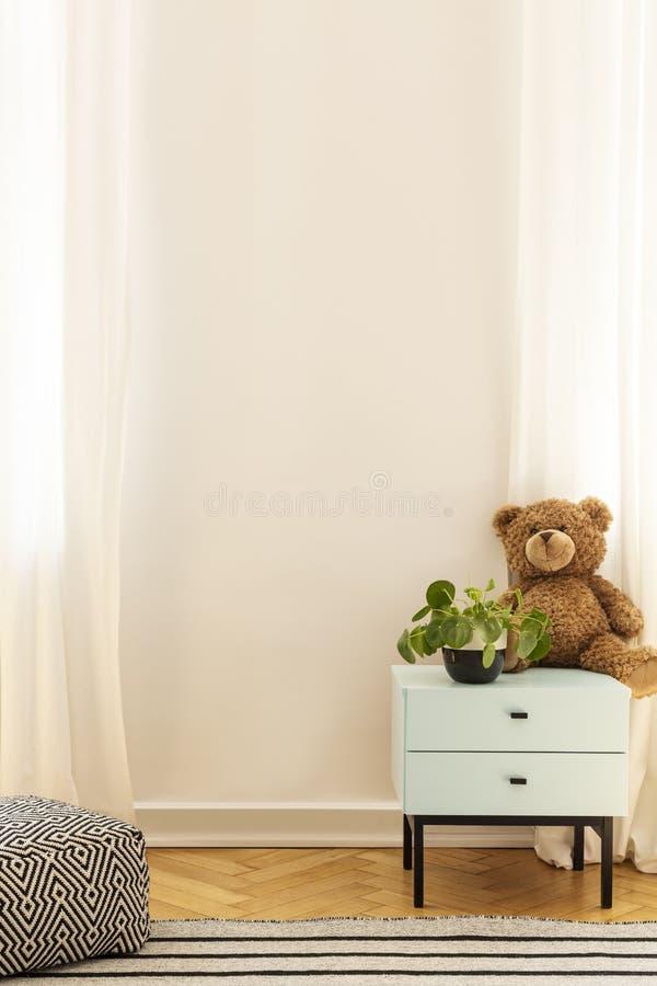 Juguete en el gabinete azul en el interior del sitio del niño con el espacio del taburete y de la copia en la pared Foto verdader foto de archivo libre de regalías