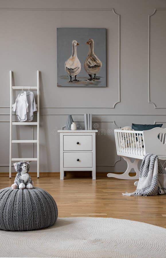 Juguete en taburete gris en dormitorio de moda del bebé con la cuna y los muebles de madera blancos, foto real con el cartel en l fotos de archivo