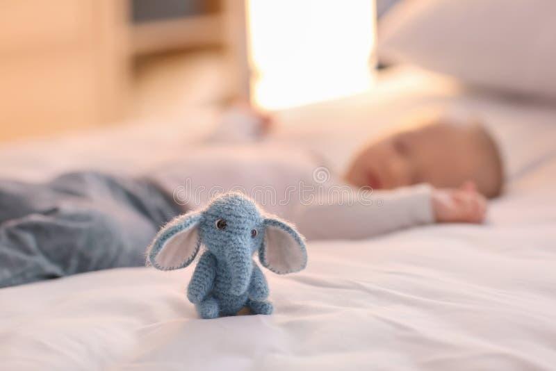 Juguete hecho punto lindo en cama cerca del niño pequeño durmiente fotografía de archivo libre de regalías