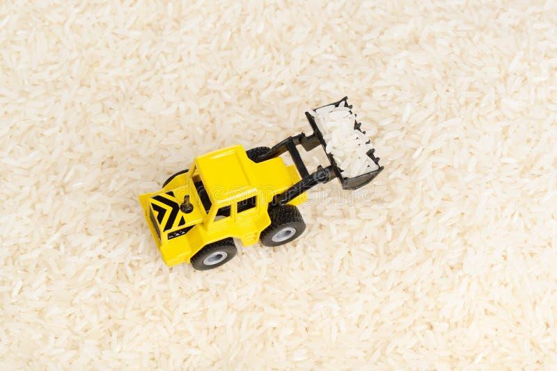 Juguete industrial del tractor en los granos del arroz fotografía de archivo
