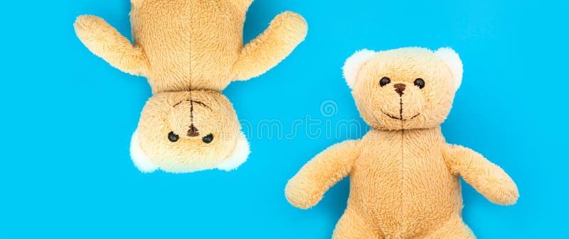Juguete marrón lindo del niño de dos osos de peluche con los brazos abiertos y las cabezas de lado a lado al revés en direcciones fotos de archivo libres de regalías