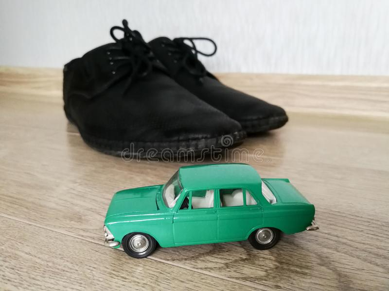 Juguete modelo del coche en comparación con los zapatos masculinos imágenes de archivo libres de regalías