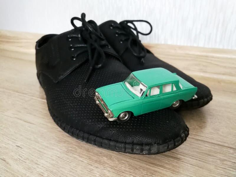 Juguete modelo del coche en comparación con los zapatos masculinos imagenes de archivo
