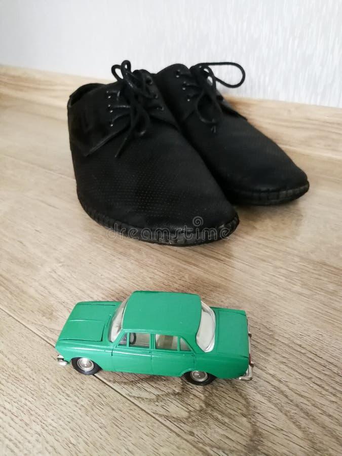 Juguete modelo del coche en comparación con los zapatos masculinos fotos de archivo