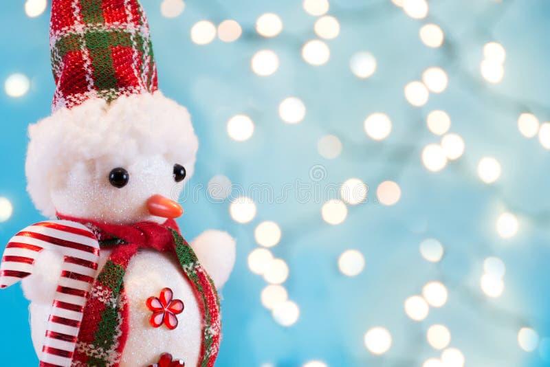 Juguete retro del muñeco de nieve con la bufanda del invierno y el sombrero y las luces del orbe de la Navidad imágenes de archivo libres de regalías