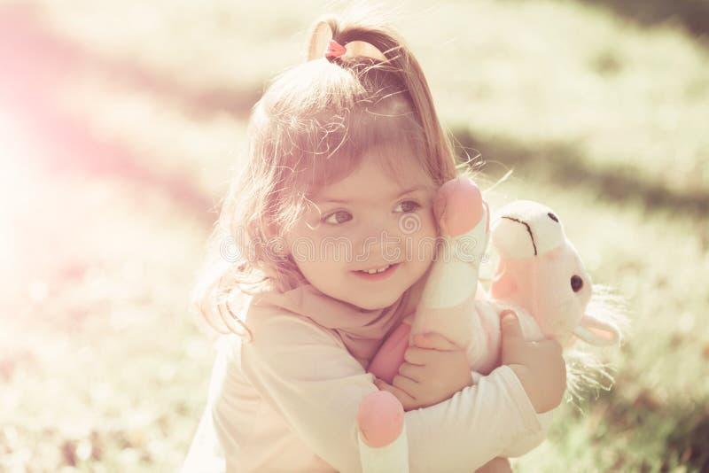 Juguete suave del caballo del abrazo de la muchacha el d?a soleado foto de archivo