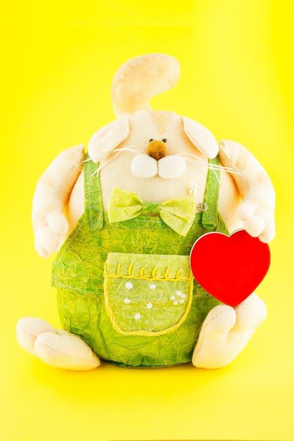 juguete suave El perro vistió las batas con el corazón del juguete del oro en su mano imagenes de archivo