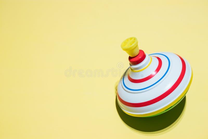 Juguete superior del giro de los niños aislamiento superior de giro del juguete en un fondo amarillo Juguetes de los niños Entret foto de archivo