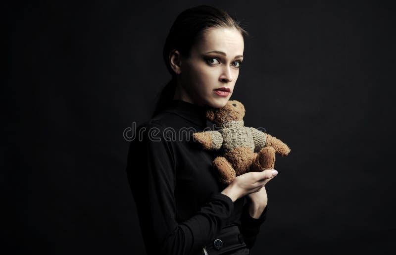 Juguete triste del oso de peluche de la tenencia de la mujer sobre fondo negro imagen de archivo