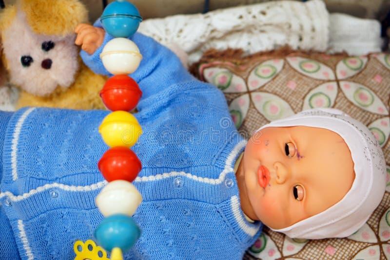 Juguete viejo, muñeca del vintage - bebé en un suéter azul en un pesebre con un perro imágenes de archivo libres de regalías
