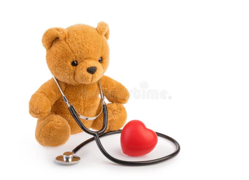 Juguete y estetoscopio del oso el concepto médico de la pediatría aisló blanco fotos de archivo libres de regalías