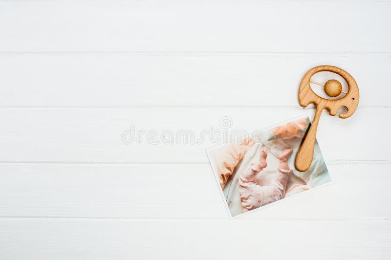 Juguete y foto de madera del bebé en el fondo de madera blanco imagen de archivo