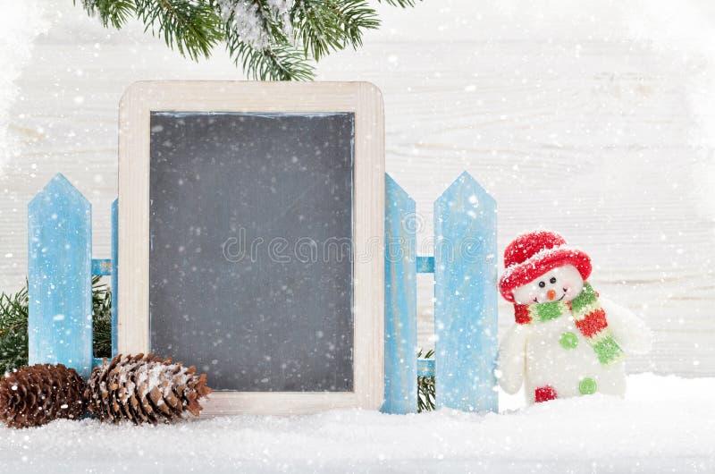 Juguete y pizarra del muñeco de nieve de la Navidad foto de archivo