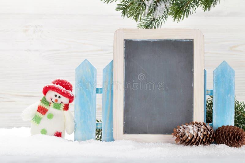 Juguete y pizarra del muñeco de nieve de la Navidad fotografía de archivo