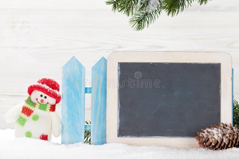 Juguete y pizarra del muñeco de nieve de la Navidad imagen de archivo