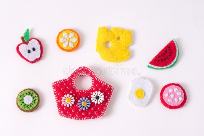 Juguetes bajo la forma de comida y frutas hechas a mano del fieltro en un blanco imagen de archivo