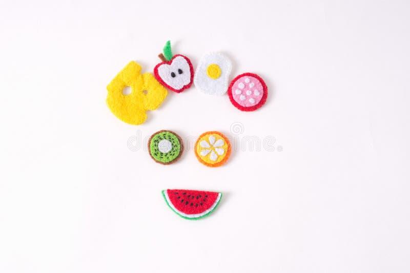 Juguetes bajo la forma de comida y frutas hechas a mano del fieltro en un blanco fotografía de archivo