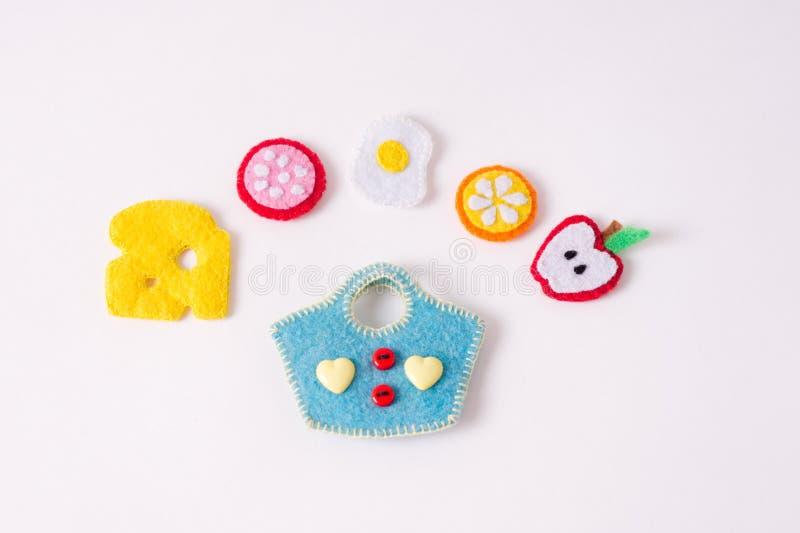 Juguetes bajo la forma de comida y frutas hechas a mano del fieltro en un blanco foto de archivo libre de regalías