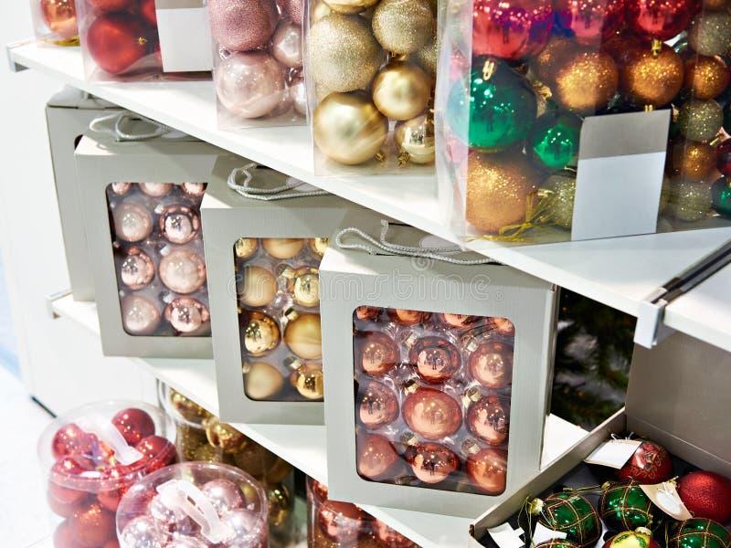 Juguetes coloreados de las bolas para el árbol de navidad en tienda fotografía de archivo