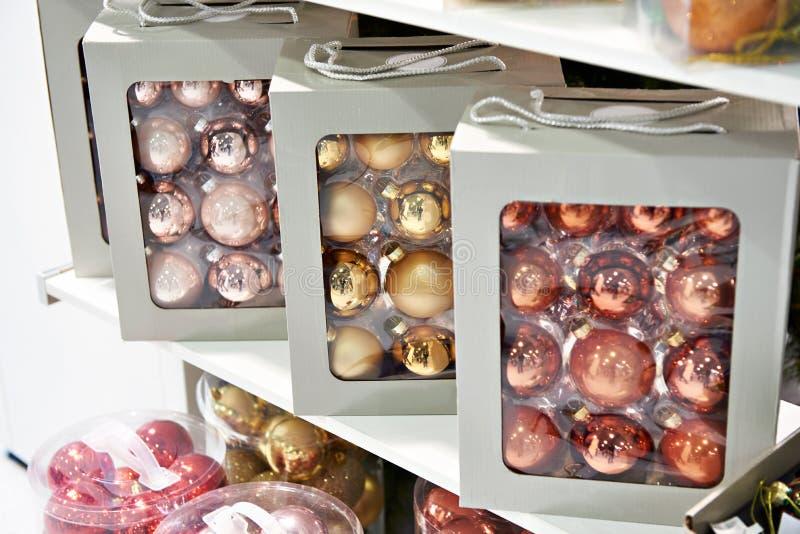 Juguetes coloreados de las bolas para el árbol de navidad en tienda fotos de archivo