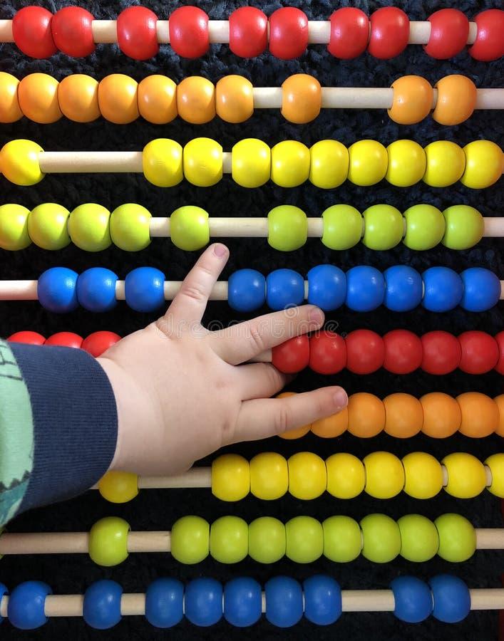 Juguetes coloridos con la mano del niño foto de archivo