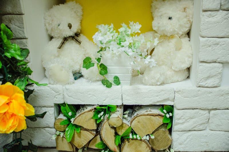 Juguetes con las flores en la chimenea, leña imagen de archivo libre de regalías