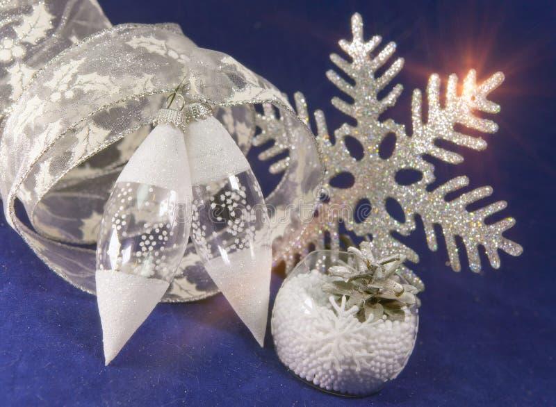 Juguetes de cristal blancos del ` s del Año Nuevo de un carámbano, de una cinta del regalo y de un copo de nieve decorativo en un imagenes de archivo