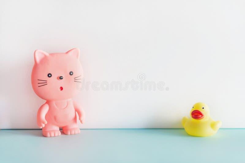 Juguetes de goma en fondo azul y blanco Un gato de goma rosado y un pato de goma amarillo que se unen Juguetes del ba?o foto de archivo